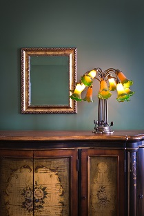 Close-up of interior design architecture with classical theme. A art Nouveau lighting fixture with mirror on a cabinet. Photographed in vertical format with copy space.