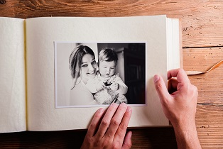 Mothers day composition. Hands of unrecognizable man holding a photo album, black-and-white picture. Studio shot on wooden background.