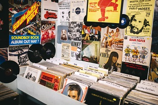 Records for sale, Record Shop. Pop music posters, advertising bands, on to the walls of a shop selling vinyl records.