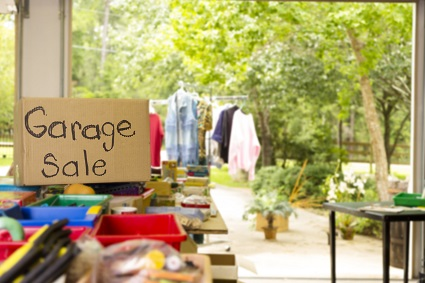 Consumerism: Garage sale sign posted in suburbs. Open for business. Home garage, yard sale in summer season. Tables set up with many rows of discarded household items.