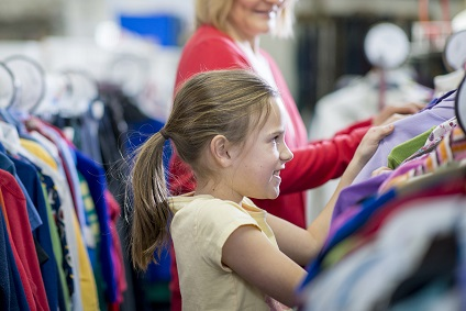 A little girl is looking through a rack of clothing at a second hand store.